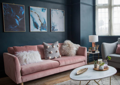 Living-room-makeover-with-dark-blue-walls-pink-sofa-and-gold-accessories-2